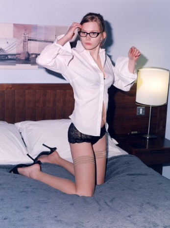 Girl on bed in high heels for GQ Magazine by Justin de Deney