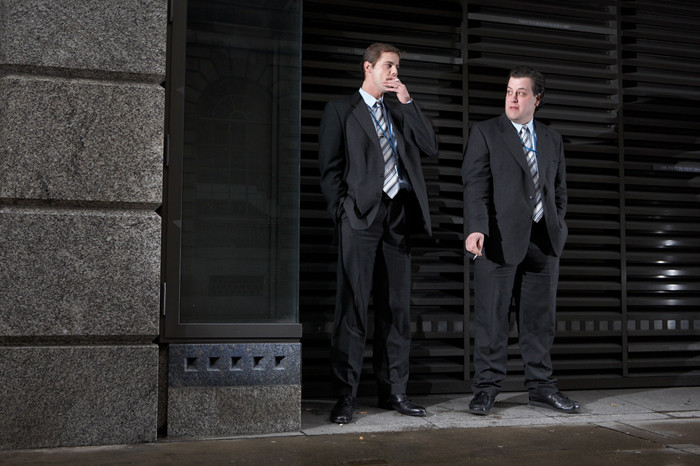 Security Guards Smoking Outside by Justin de Deney